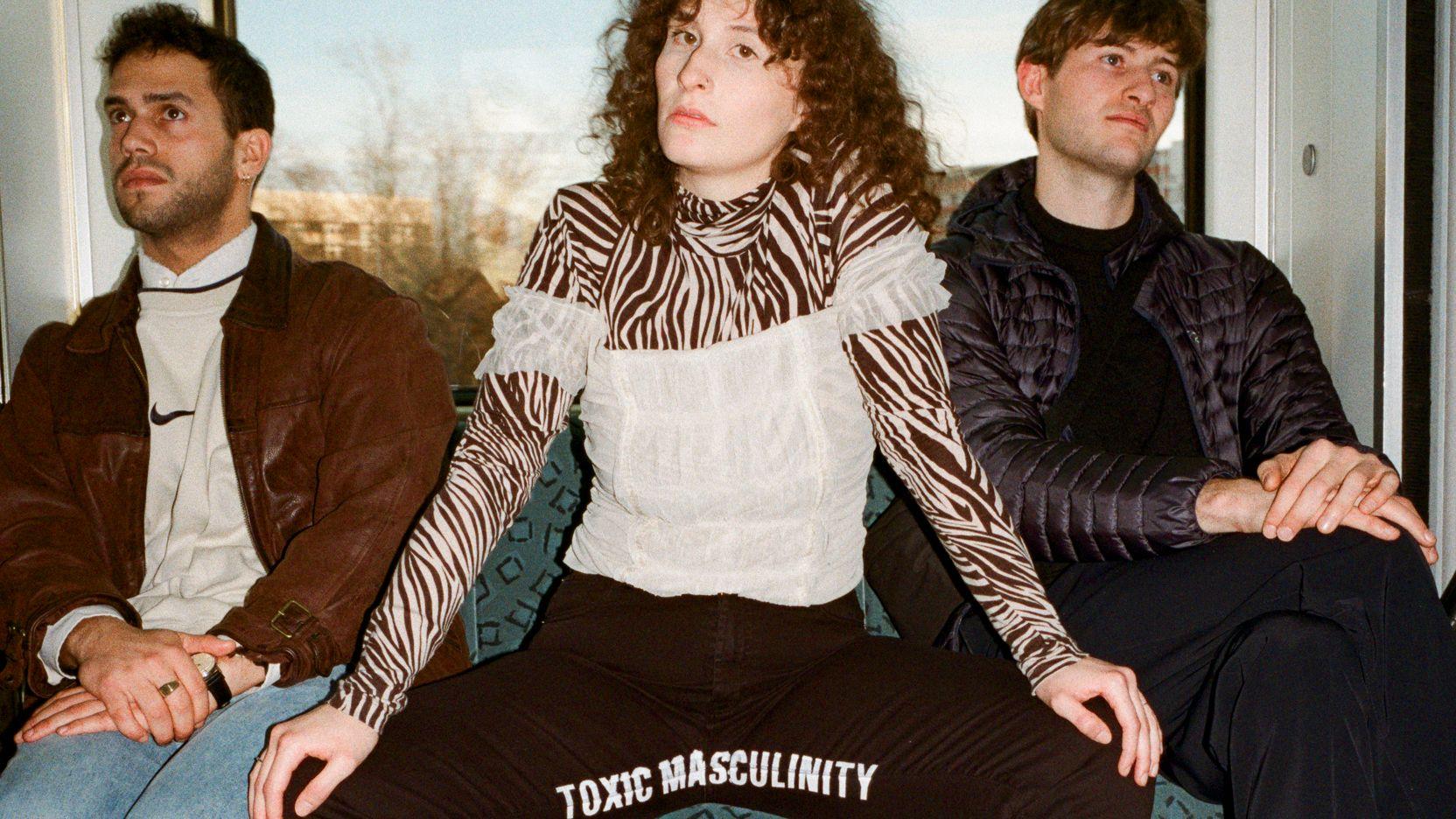 """Eine Frau sitzt breitbeinig zwischen zwei Männern auf einer Bank in einer U-Bahn. Auf ihrer Hose steht im Schritt """"Toxic Masculinity""""."""