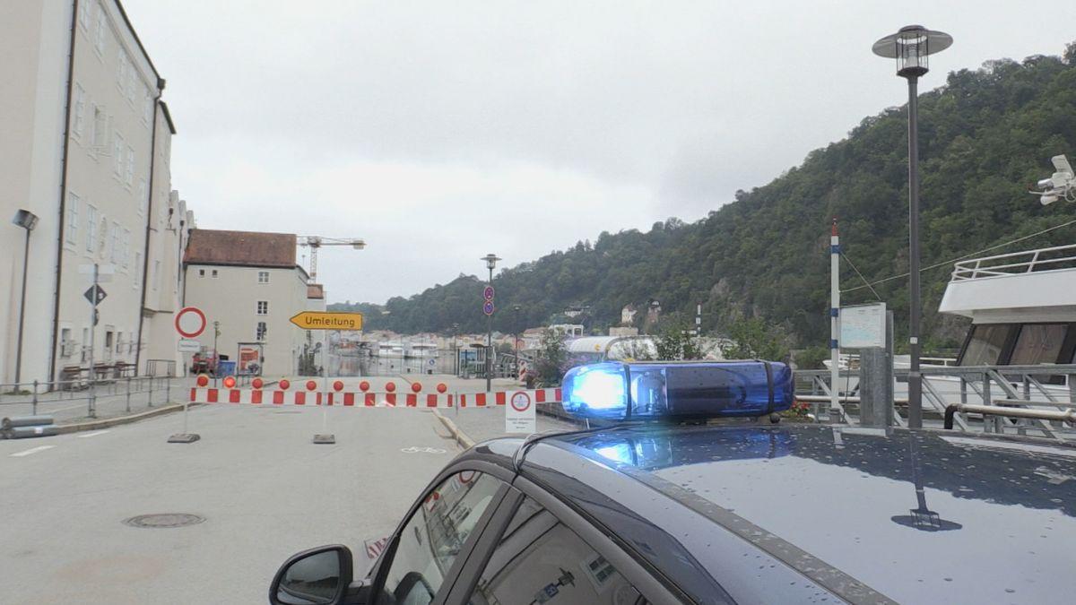 Ein Polizeiauto mit Blaulicht steht vor Hochwassersperren in Passau.
