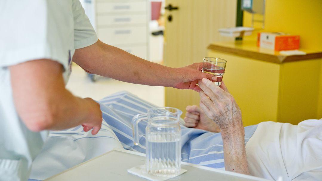 Ein Pfleger reicht ein Glas Wasser ans Bett