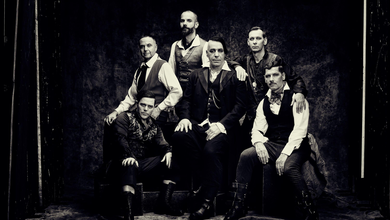Die sechs Mitglieder der Band Rammstein sitzen neben- und hintereinander, Sänger Till Lindemann in der Mitte