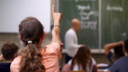 Eine Schülerin der fünften Klasse hebt im Unterricht den Finger.   Bild:dpa-Bildfunk