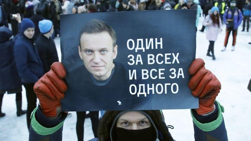 """Ein Demonstrant hält ein Plakat mit einem Bild von Nawalny und dem Spruch """"Einer für alle und alle für einen""""."""