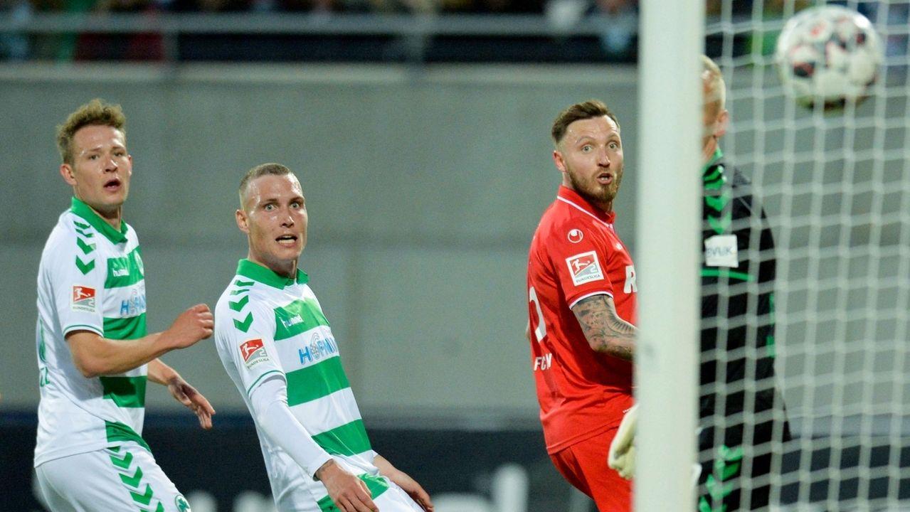 Fürths Paul Jaeckel und David Raum sowie Kölns Marco Höger sehen den Ball hinterher, der ins Tor fliegt.