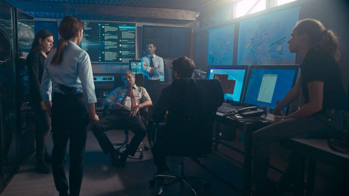 """Man sieht in einer Szene aus """"La Jauría - Die Meute"""" verschiedene Personen in einem Kontrollraum der Polizei"""