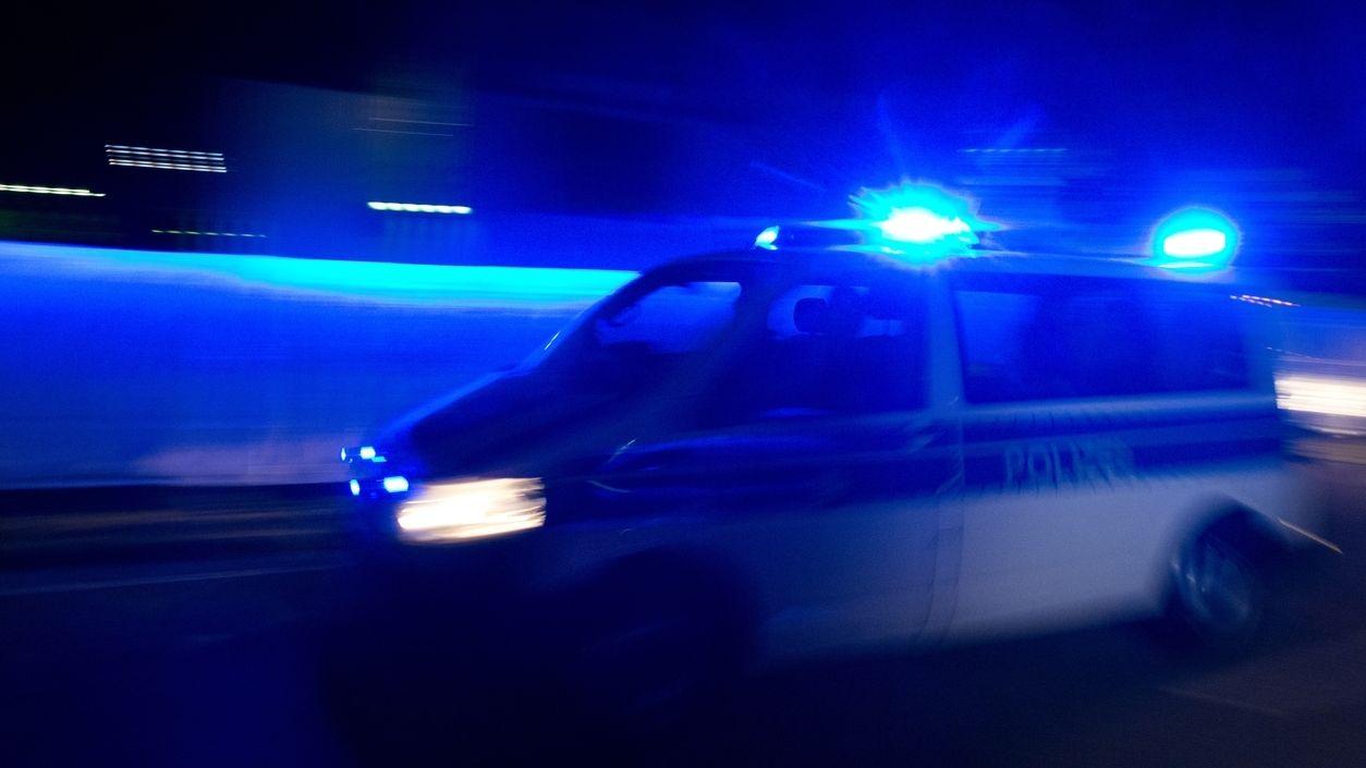 Polizeiauto fährt mit Blaulicht durch die Nacht (Symbolbild).