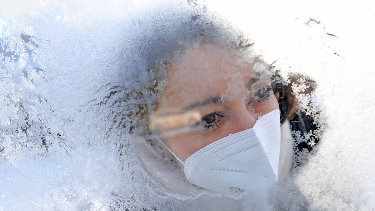 Junge Frau mit Mundschutz hinter einer Scheibe mit Eisblumen