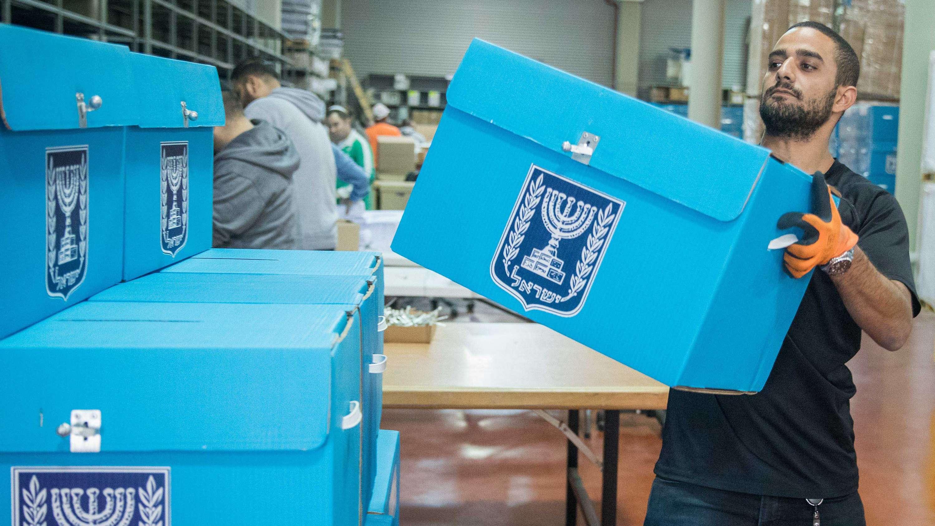 Ein mann trägt in einem Lager eine Wahlurne für die bevorstehenden Wahlen in Israel