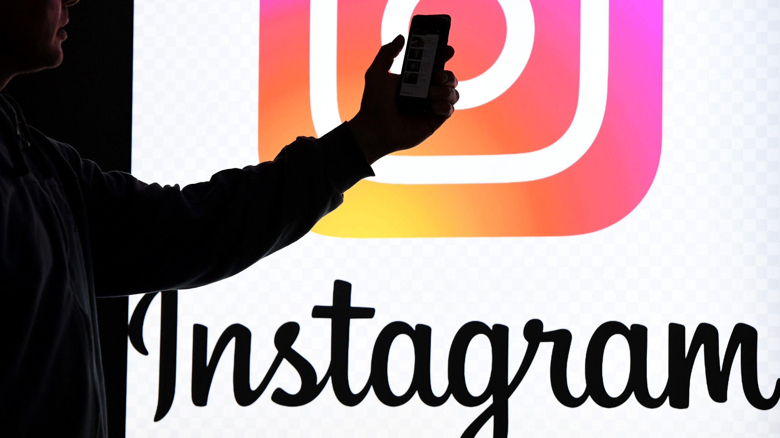 Ein Mann hält ein Smartphone vor einem Monitor mit dem Logo von Instagram.