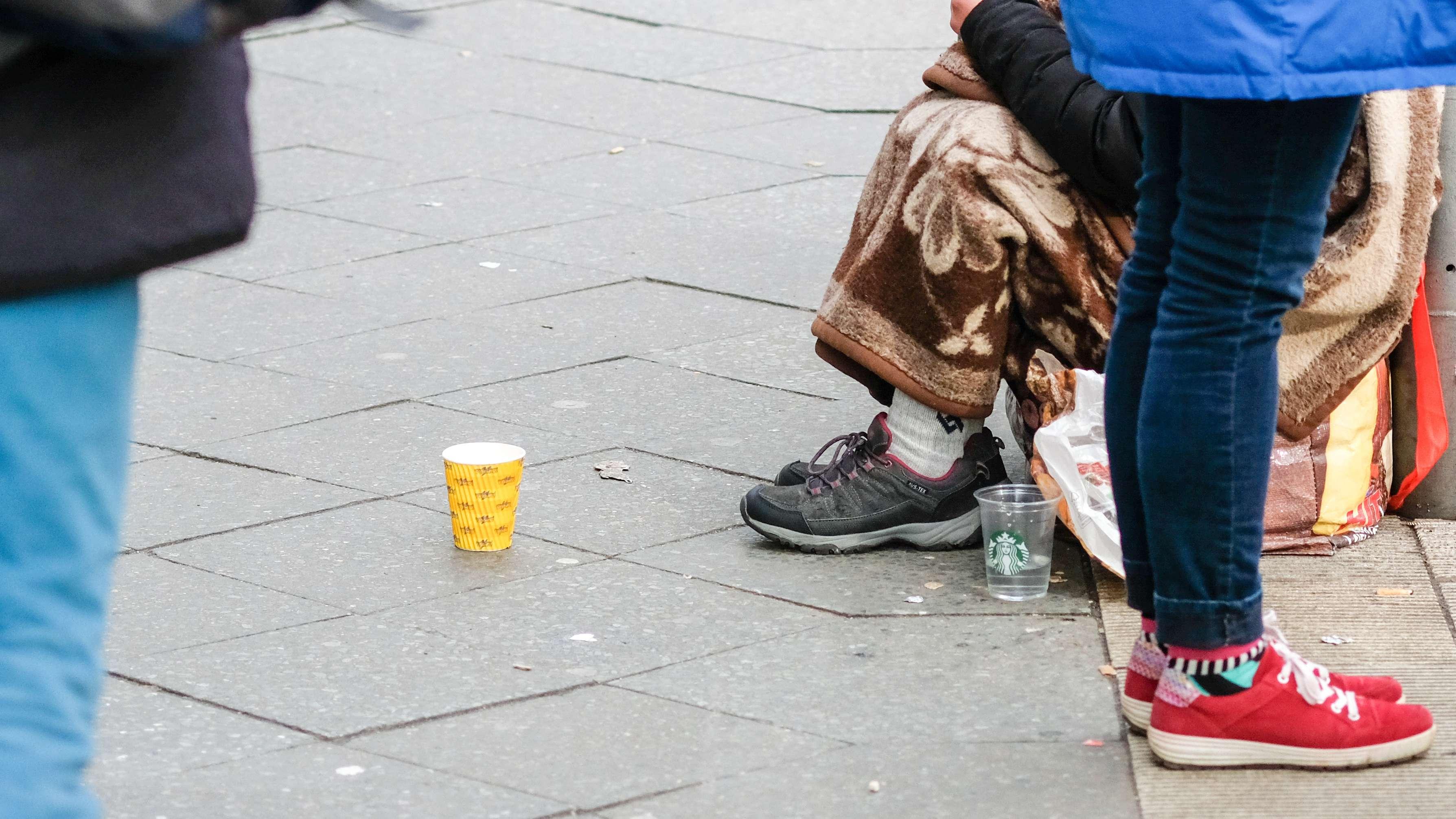 Ein Bettler in einer Fußgängerzone hat einen Papierbecher vor sich aufgestellt
