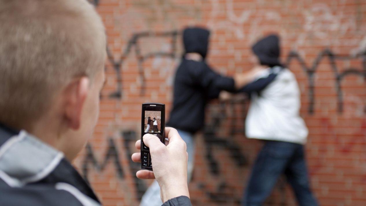 Zwei Jugendliche rangeln, ein dritter filmt mit dem Handy