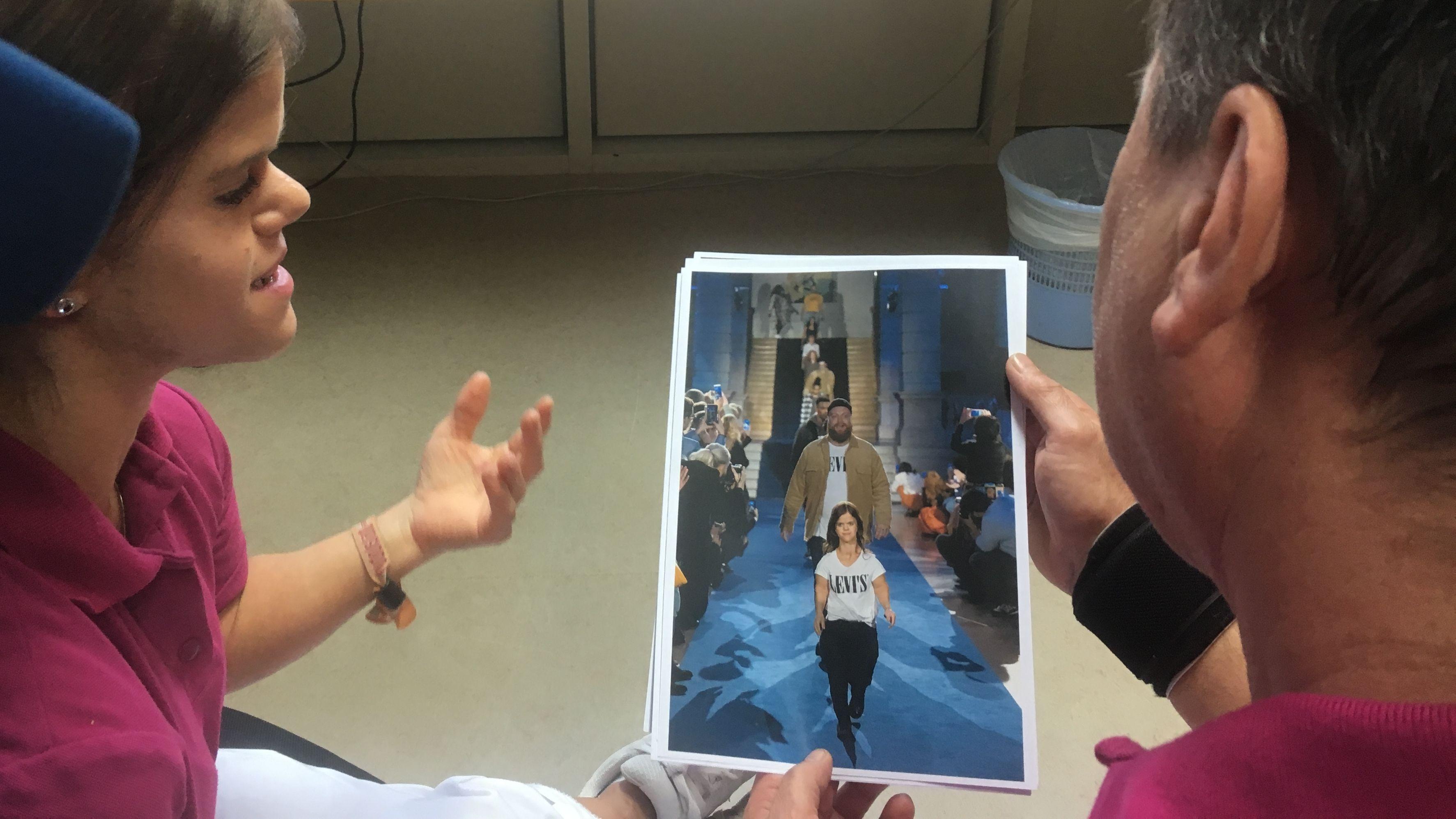 Zwei Menschen betrachten ein Foto, auf dem eine kleinwüchsige Frau als Fotomodell auf einem Laufsteg zu sehen ist.