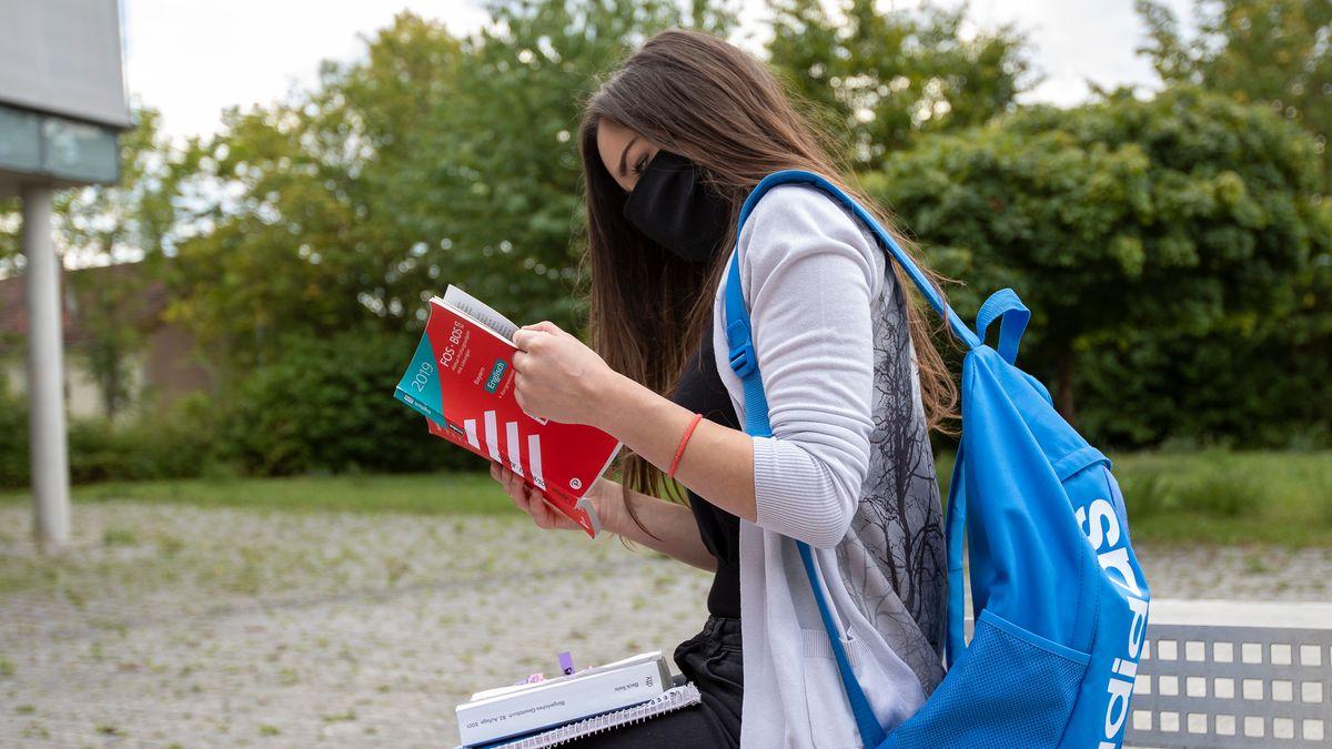 Eine Schülerin vor ihrem Gymnasium