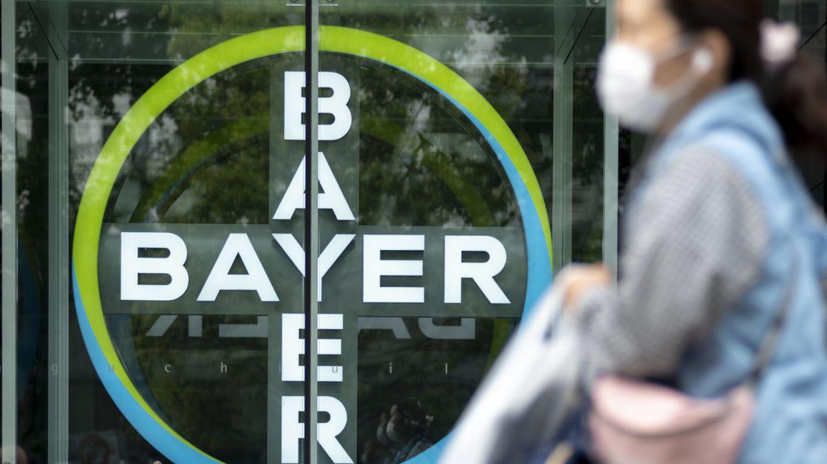 Bayer-Logo und Frau mit Mundschutz