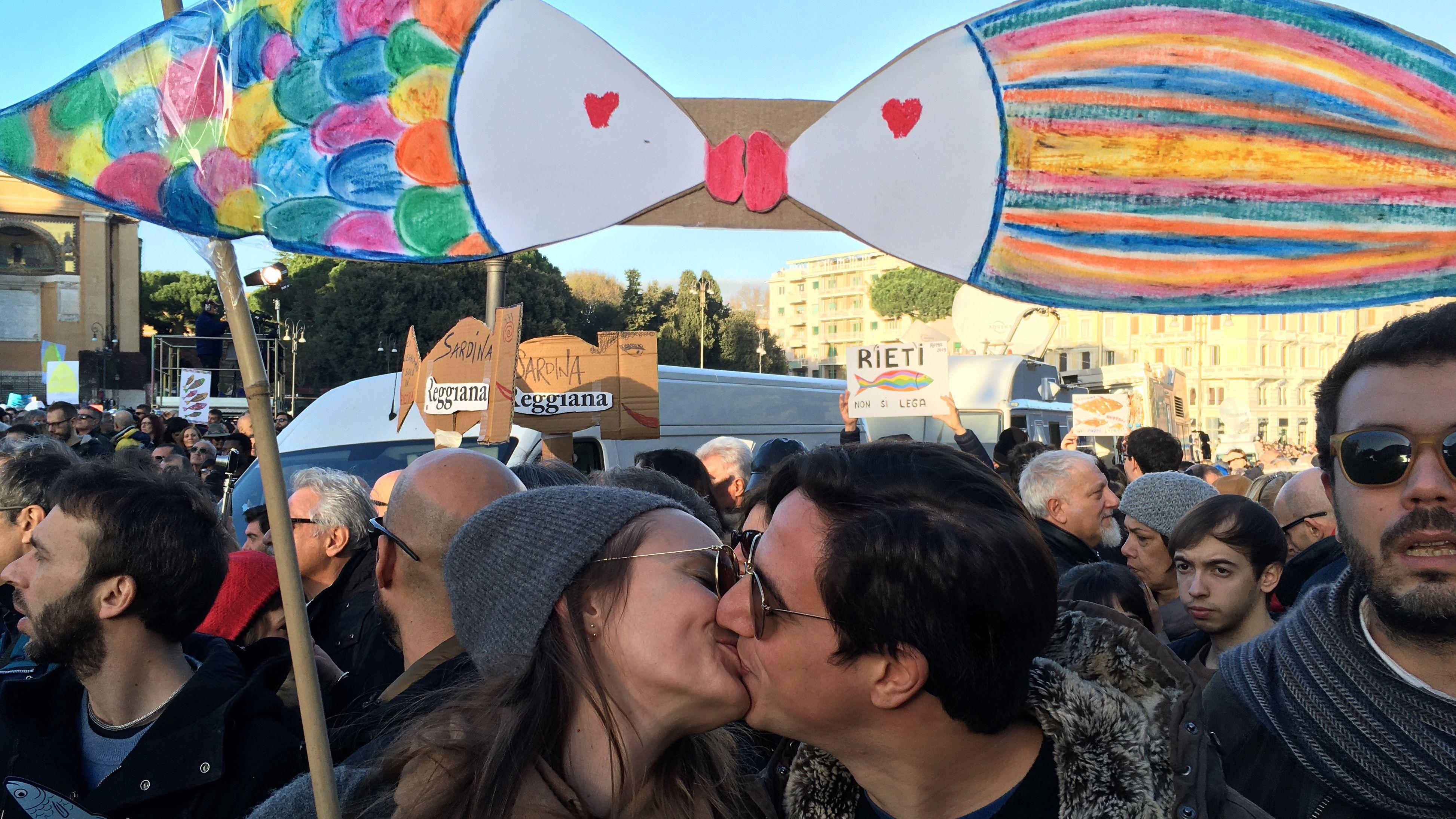 Zwei Demonstranten küssen sich unter Sardinensymbolen