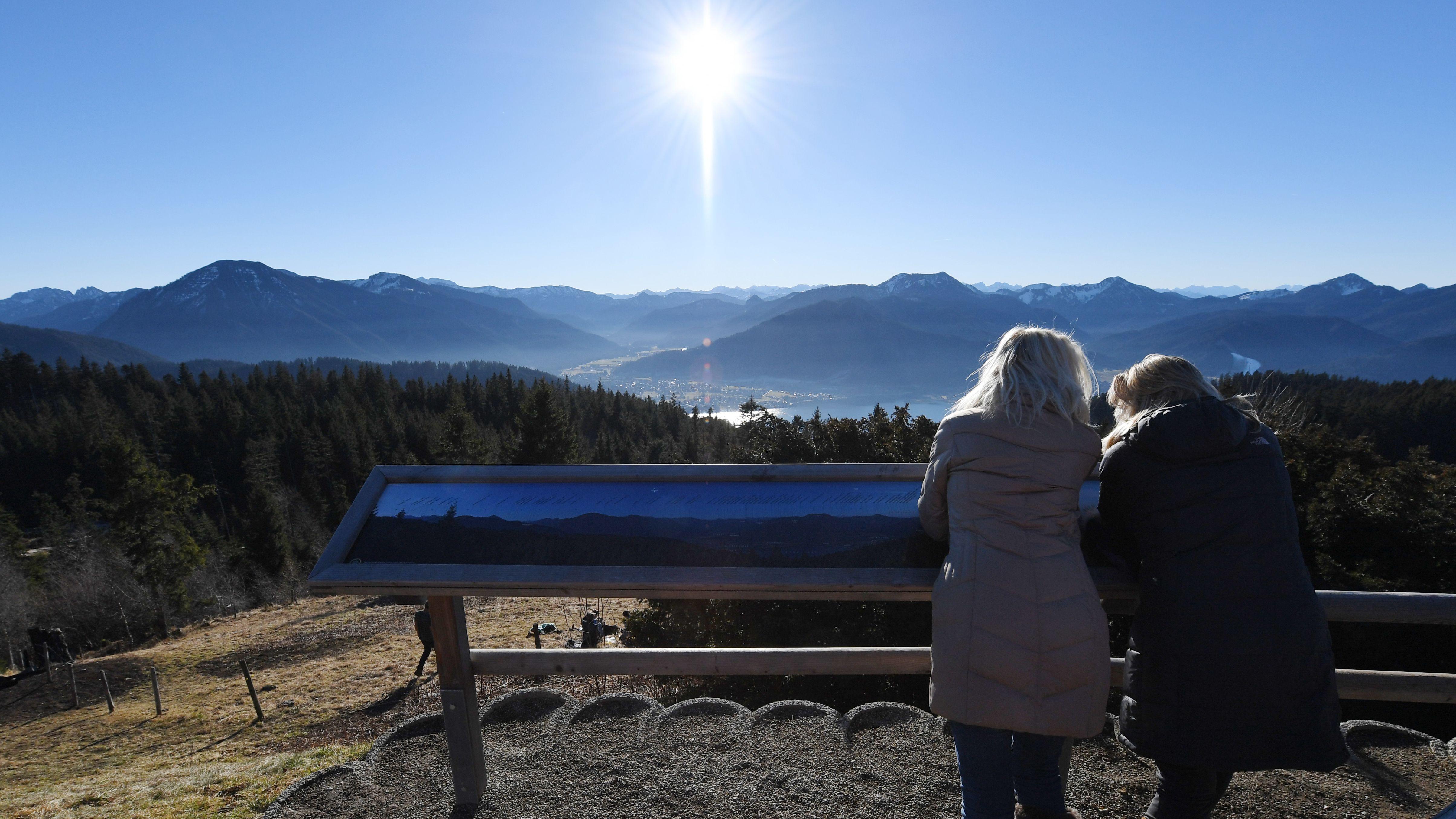 Zwei Frauen stehen bei der Neureuth Alm und sehen sich bei Sonnenschein das Bergpanorama an
