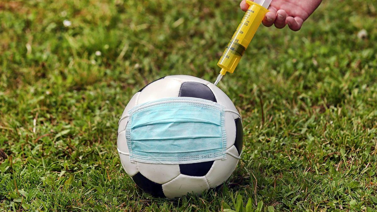 Fußball mit Corona-Schutzmaske bekommt eine Spritze