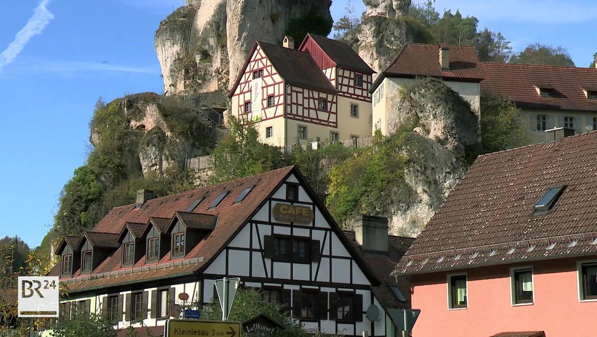 Fachwerkhäuser und im Hintergrund ein Felsen.