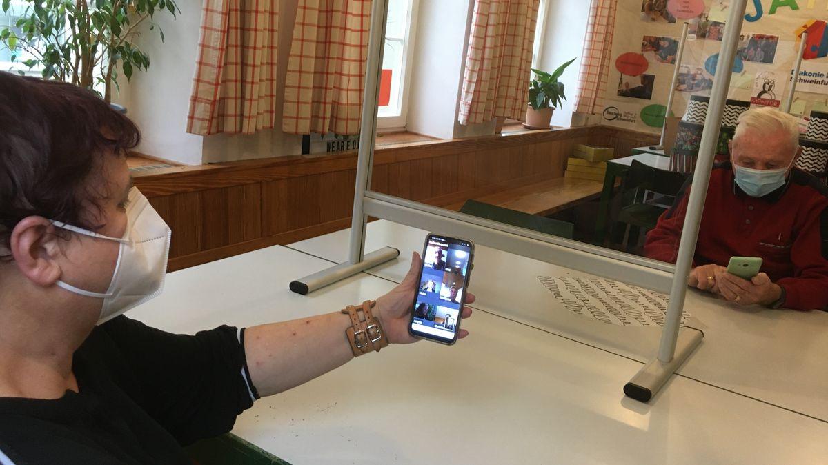 Ein Mitarbeiterin der Diakonie Schweinfurt erklärt einem Rentner, wie eine Videokonferenz auf dem Smartphone funktioniert.