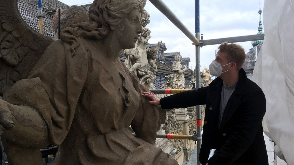 Restaurator Silas Ploner betrachtet eine Figur auf der Stadtfassade der Würzburger Residenz