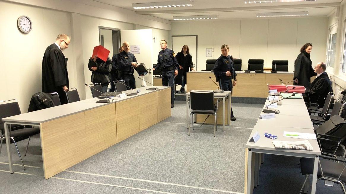 Im Aschaffenburger Cold Case-Prozess betritt der Angeklagte den Gerichtssaal. Er hält sich eine Mappe vor das Gesicht.