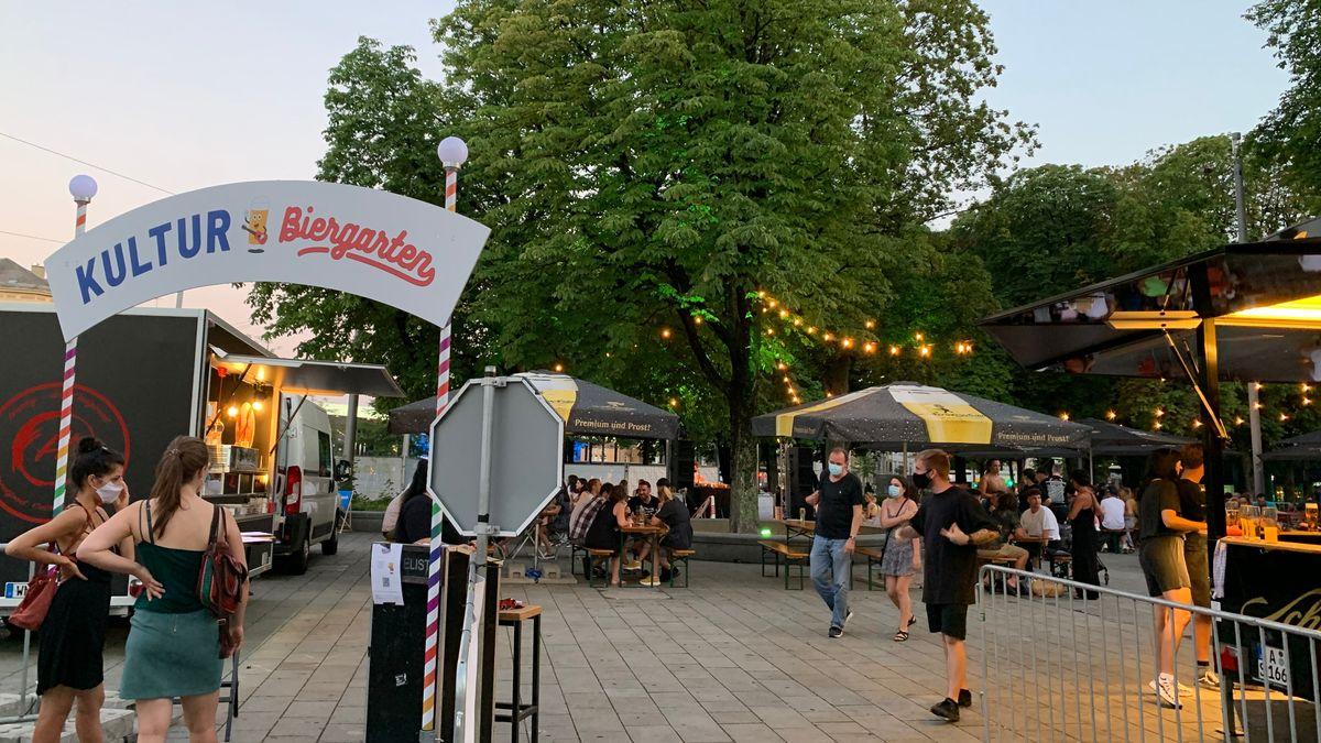 Kultur-Biergarten am Augsburger Königsplatz mit Bierbänken und mobilen Bars unter Lichterketten