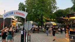 Kultur-Biergarten am Augsburger Königsplatz mit Bierbänken und mobilen Bars unter Lichterketten    Bild:BR/Laura Hunger