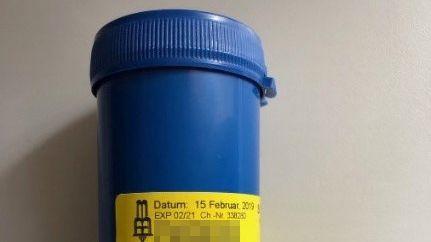 Blaue Plastikdose mit gelbem Etikett. In solchen Dosen wurden die Präparate wohl abgegeben.