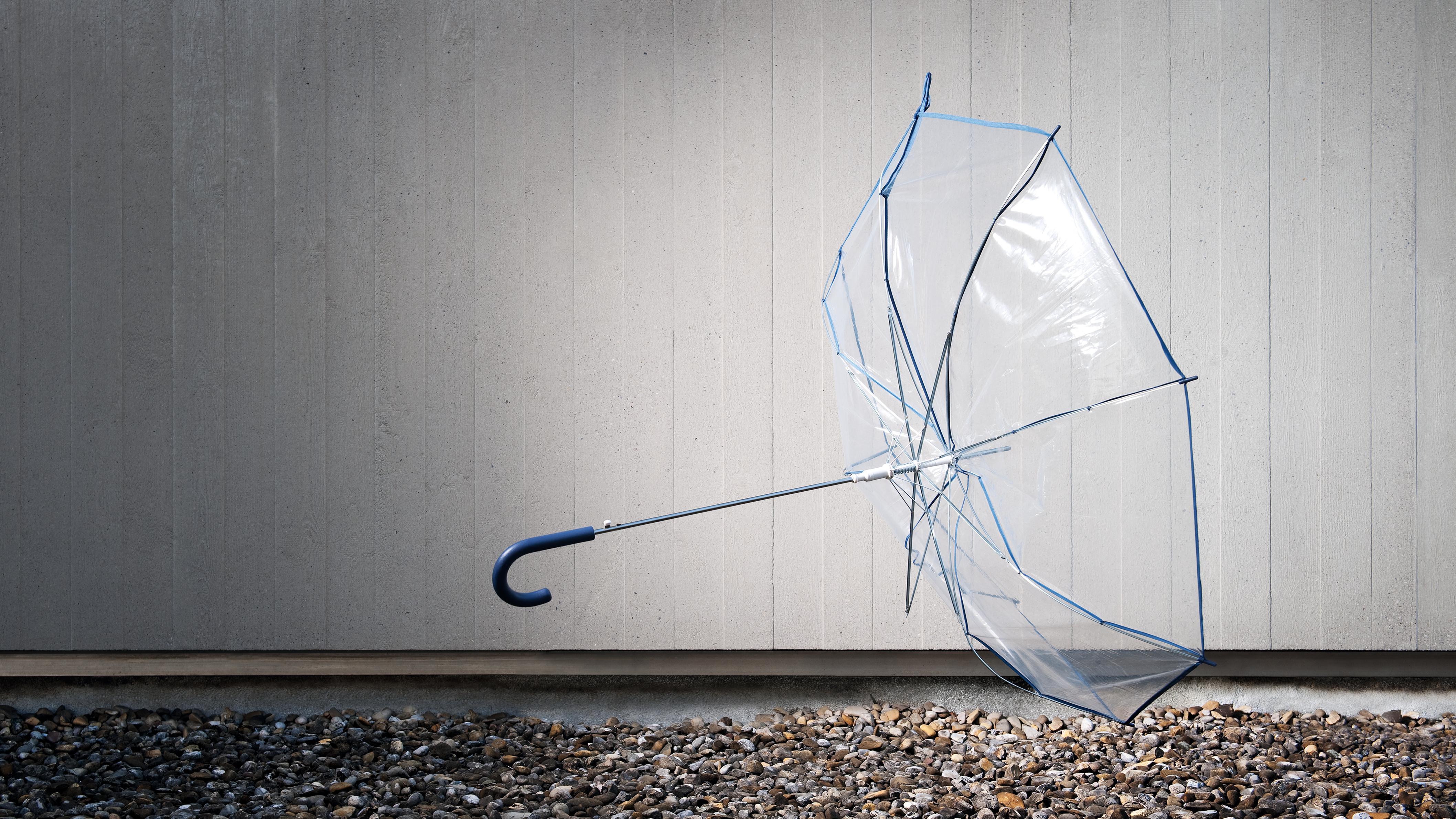 Ein durchsichtiger Regenschirm wird vom Wind weggeweht.
