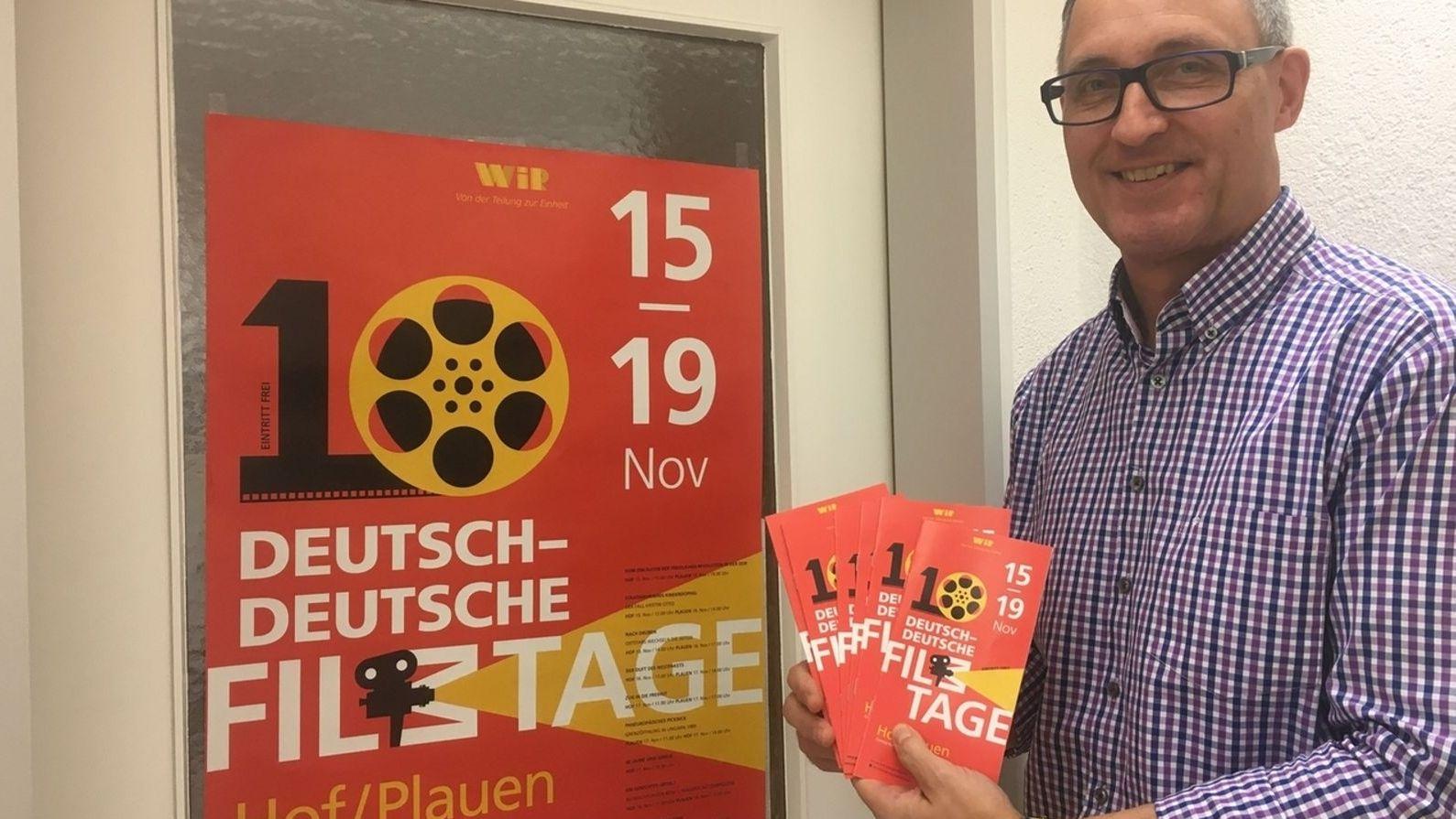 Ein  Mann hält mehrere Flyer von den Deutsch-Deutschen Filmtage in der Hand, dahinter ein rotes Plakat mit einer Filmrolle, das auf das Filmfestival in Hof und Plauen hinweist.