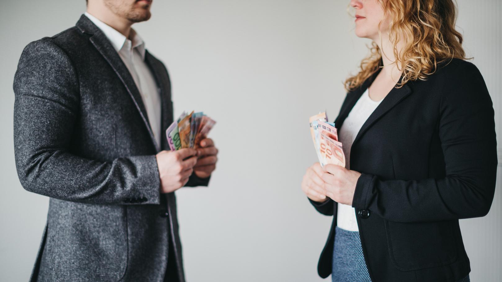 Mann und Frau mit Geldscheinen in der Hand stehen sich gegenüber
