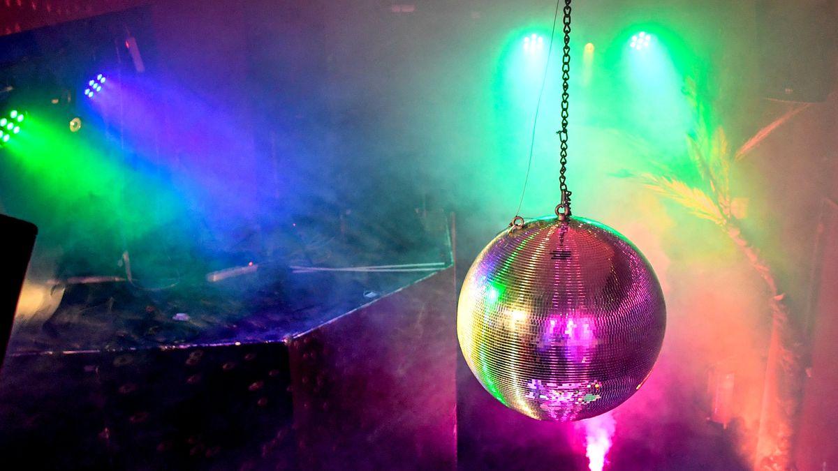 Eine Discokugel hängt in einem Raum mit Kunstnebel und buntem Party-Licht