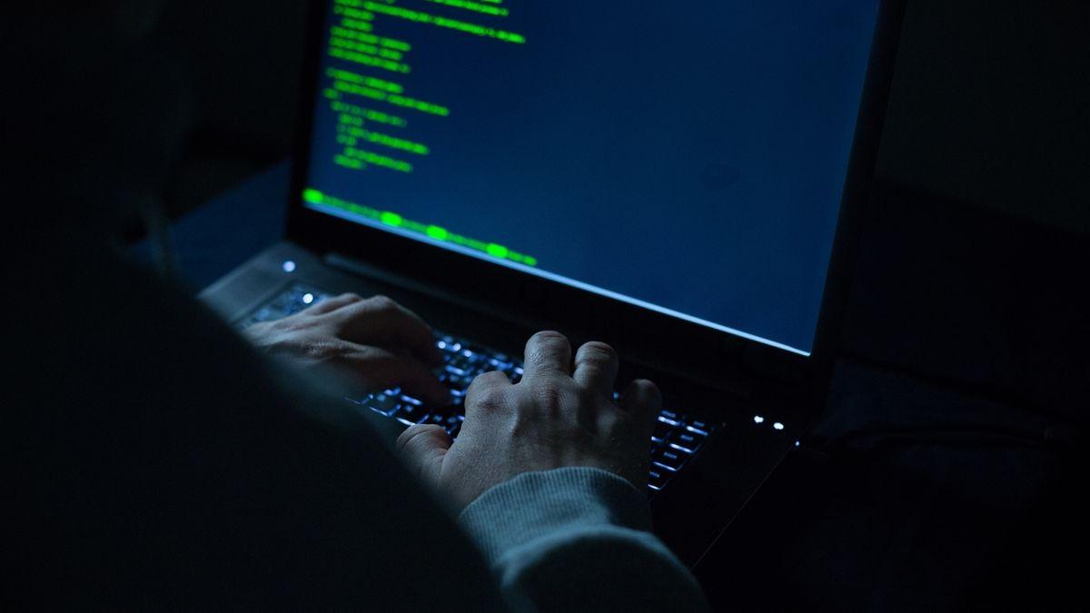 Ein Mensch sitzt vor einem Laptop