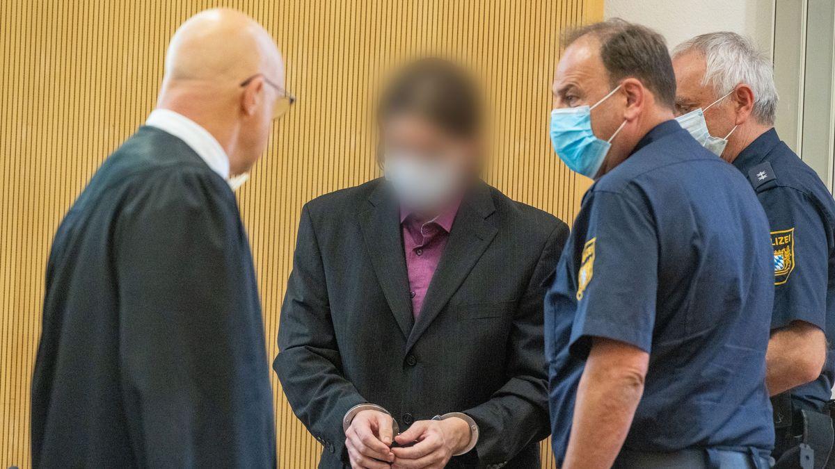 Der Angeklagte geht in Handschellen und mit Mundschutz in den Verhandlungssaal des Landgerichts, und wird dabei von Polizisten begleitet.