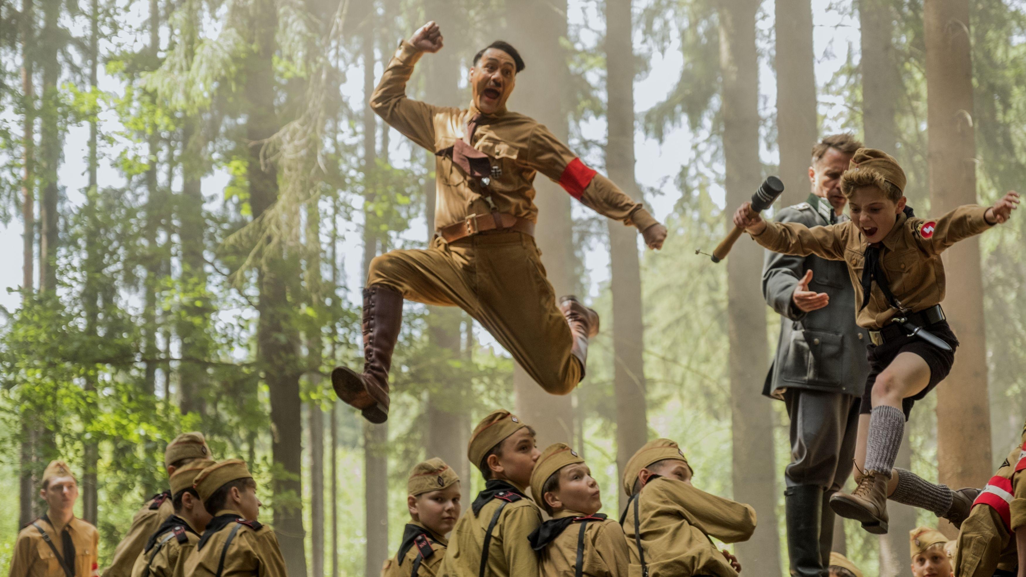 Taika Waititi als Adolf Hitler und Roman Griffin Davis als Hitlerjunge Jojo springen über die Köpfe der verdutzten Hitlerjugend durch den Wald