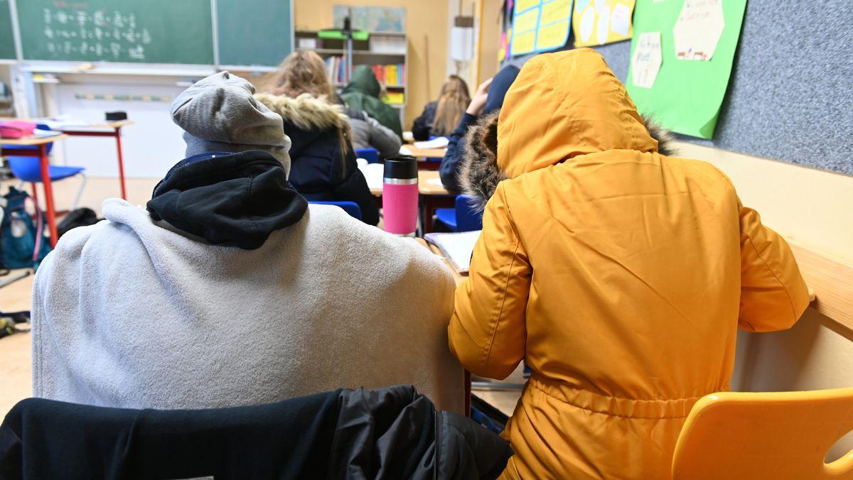 Dick in Jacken eingepackte Schüler in einem Klassenzimmer