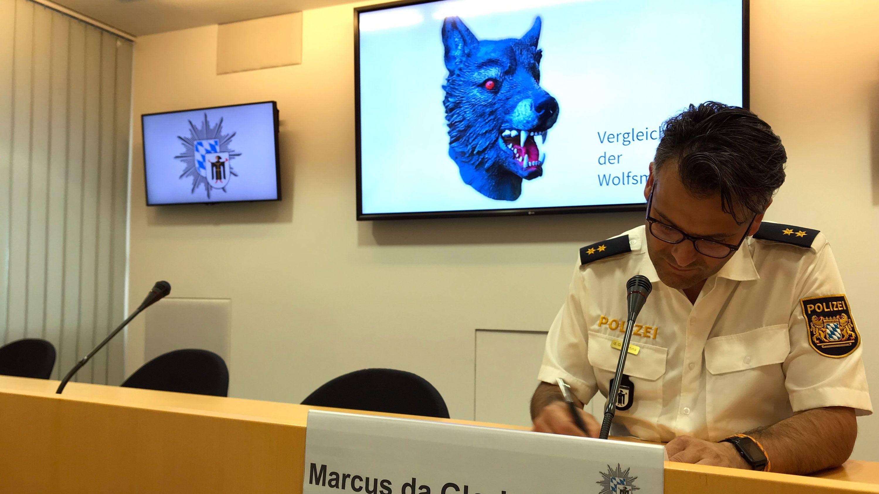 Marcus da Gloria Martins, Sprecher der Münchner Polizei, sitzt vor einem Bildschirm auf dem die Polizei ein Vergleichsbild einer Wolfsmaske präsentiert .