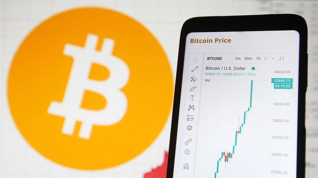 Auf dem Display eines Smartphones ist der Anstieg des Bitcoin-Kurses zu sehen.