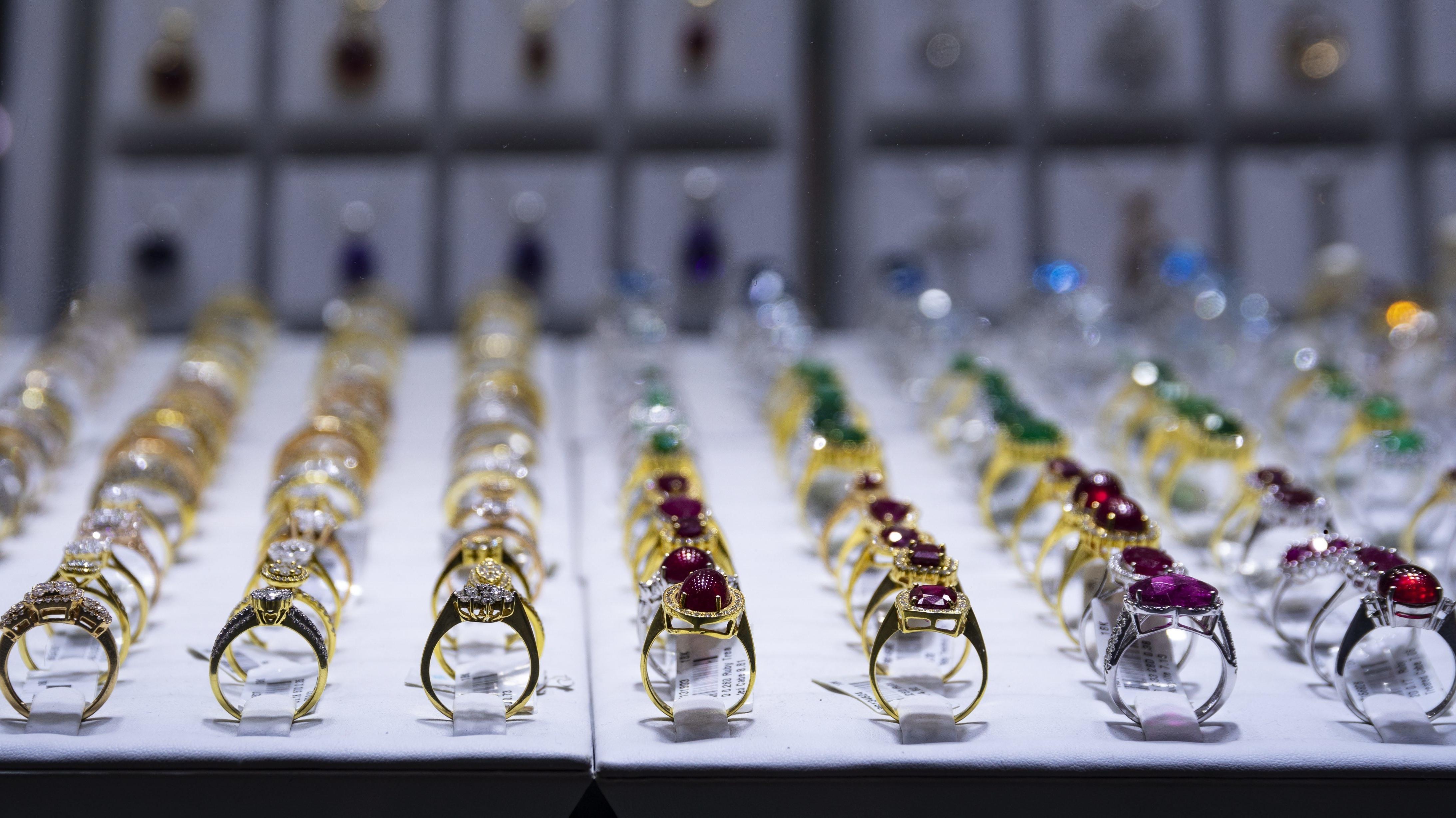 Symbolbild: Mit Edelsteinen besetzte Goldringe füllen die Auslage eines Geschäfts.