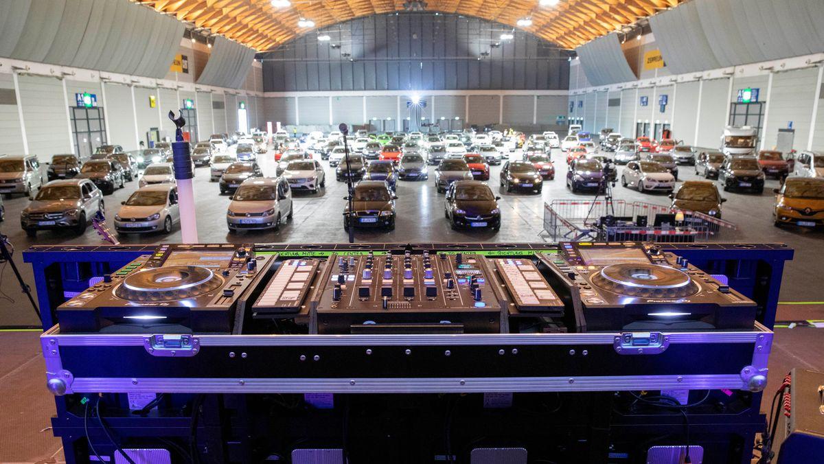 Fahrzeuge in einer Halle, im Vordergrund Mischpult eines DJs