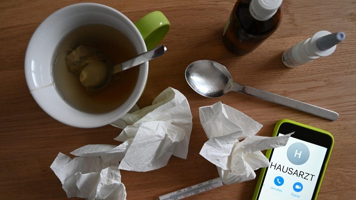 Eine Tasse Tee, zerknüllte Taschentücher, Medikamente, Fieberthermometer und ein Handy liegen auf einem Tisch (Symbolbild)