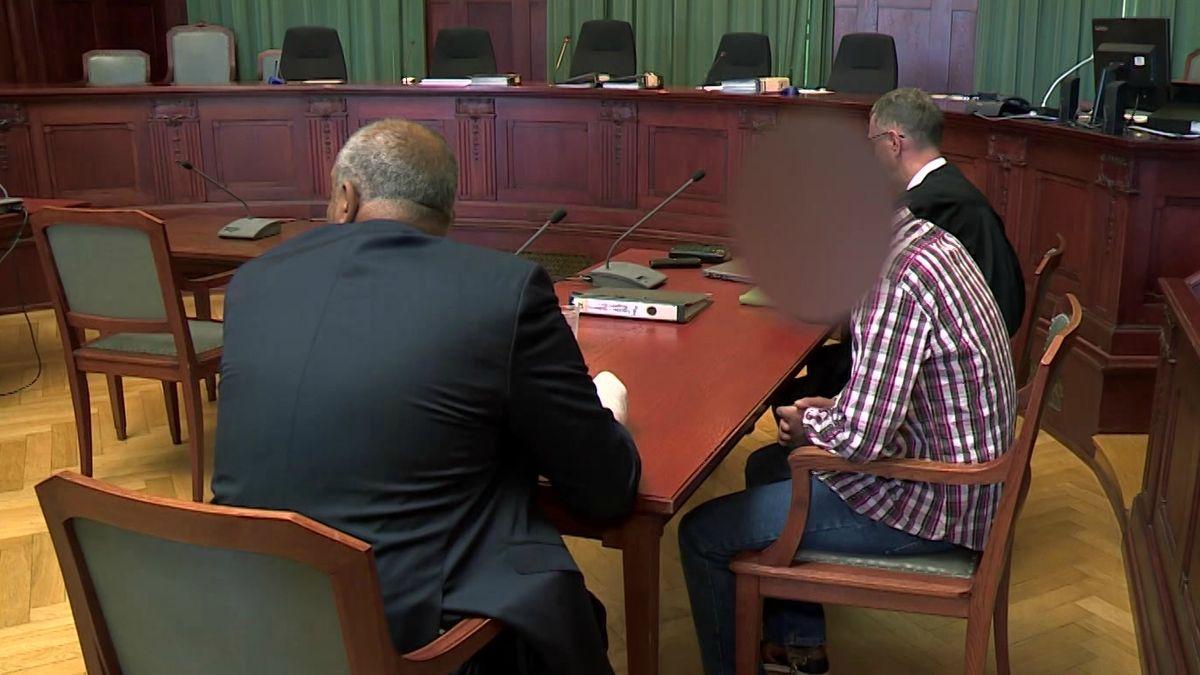 Der Angeklagte sitzt mit seinem Verteidiger und einem Übersetzer im Gerichtssaal