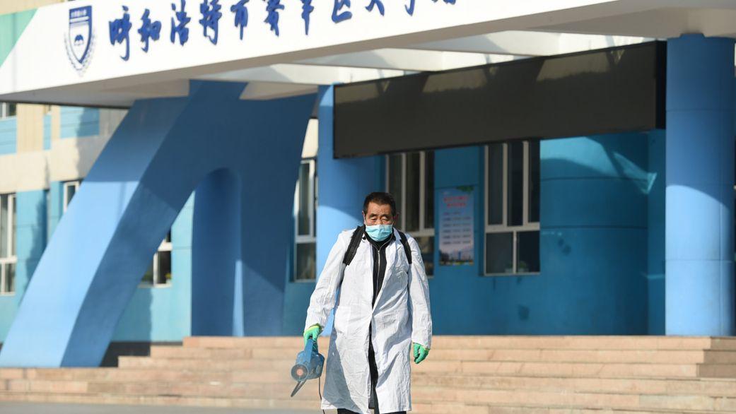 25.10.2021, China, Hohhot: Ein Mitarbeiter versprüht Desinfektionsmittel auf dem Gelände einer Grundschule in Region Innere Mongolei. Schulen und Kindergärten in Hohhot blieben am Montag einen Tag lang geschlossen, um den Campus zu desinfizieren, nachdem in letzter Zeit wieder Fälle von Covid-19 aufgetreten waren.