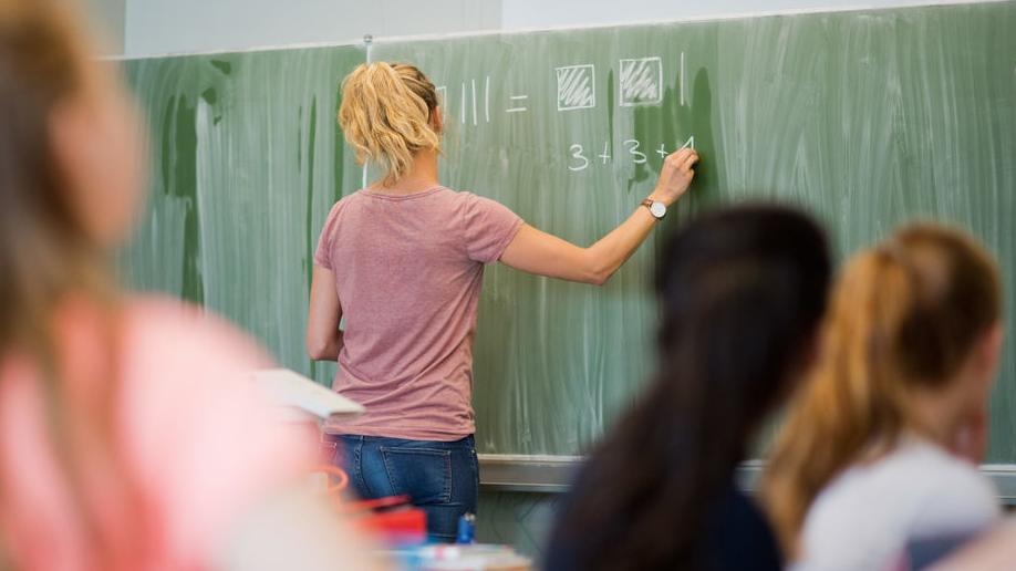 Symbolbild: Lehrerin an Schultafel. Sie schreibt mit Kreide eine Rechnung an die Tafel