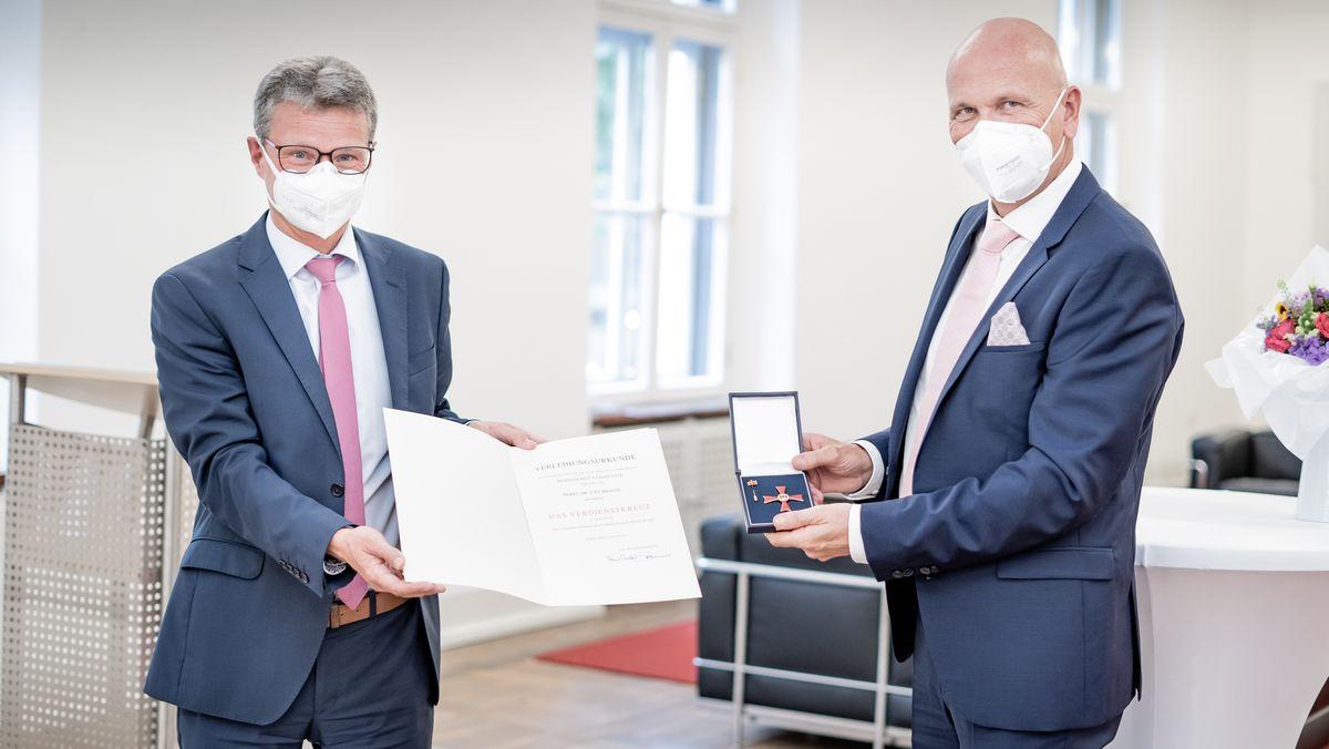 Wissenschaftsminister Bernd Sibler (li.) überreicht Gemeindetags-Chef Uwe Brandl das Bundesverdienstkreuz erster Klasse