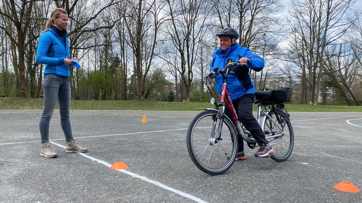 Trainerin und älterer Fahrradfahrerin.