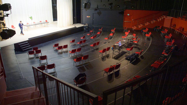 Ein Mann steht auf einer Bühne, die roten Stühle im Publikumsraum sind leer