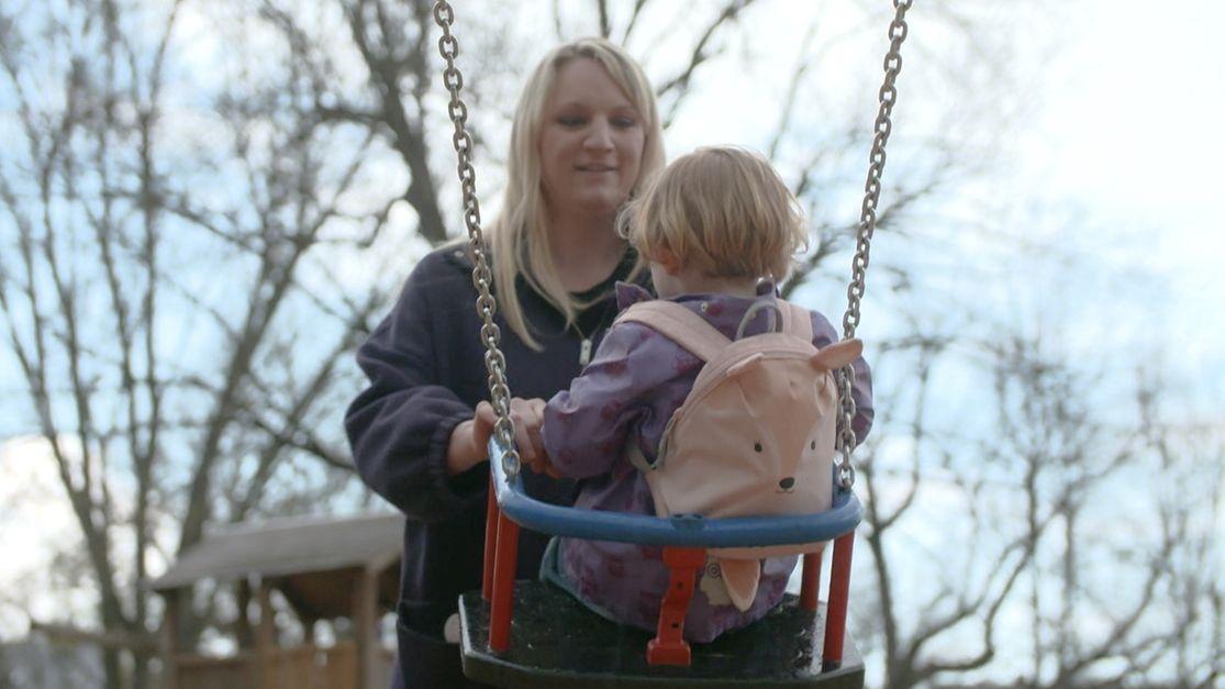 Laura Häckl mit ihrem Kind auf einem Spielplatz beim Schaukeln
