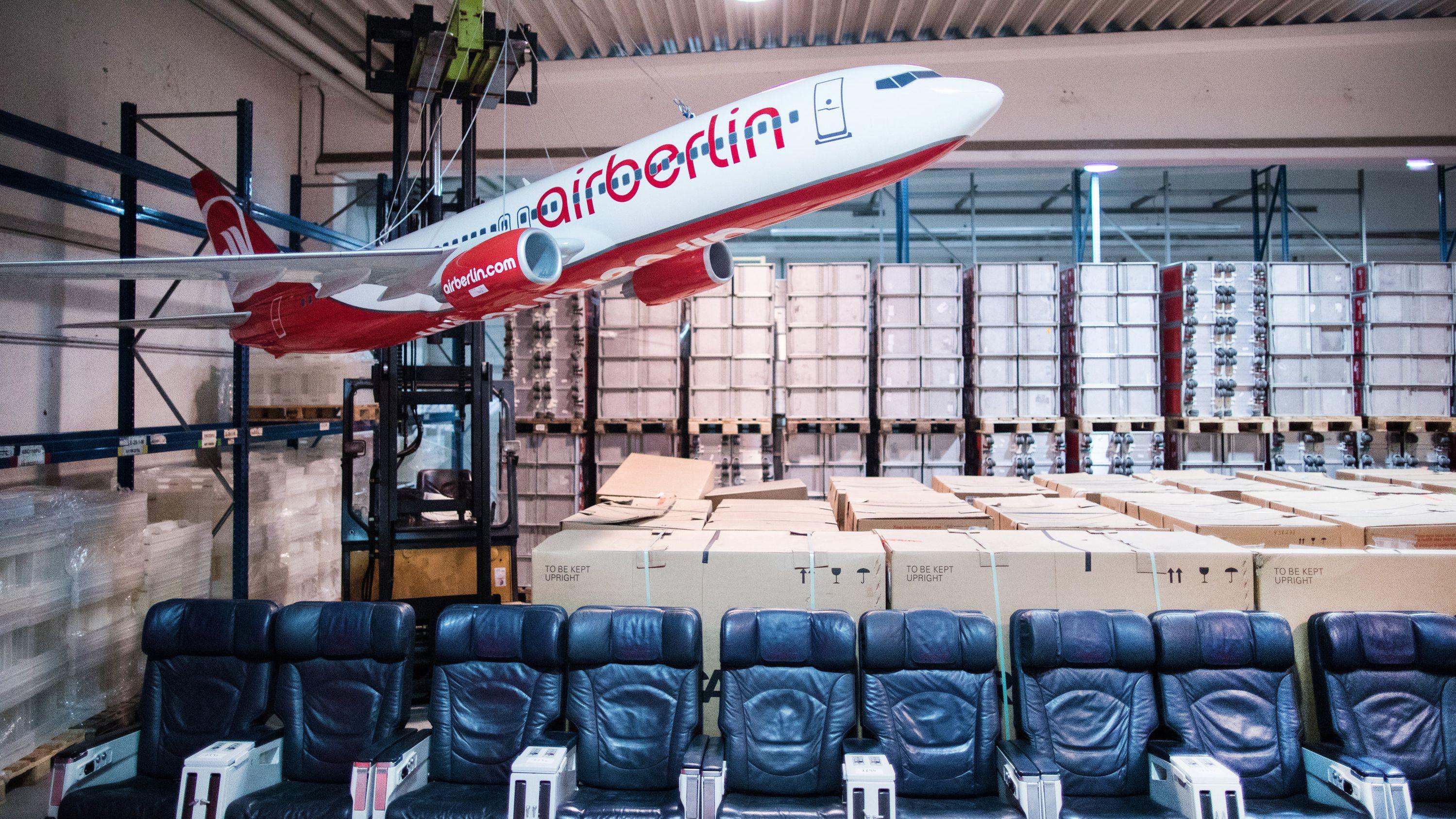 Ein großes Modell eines Air Berlin-Flugzeuges ist in einer Lagerhalle präsentiert. Darunter sind Sessel aus Flugzeugen nebeneinander gereiht.