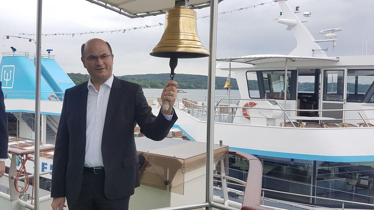 Heimatminister Albert Füracker läutet eine Schiffsglocke in Starnberg