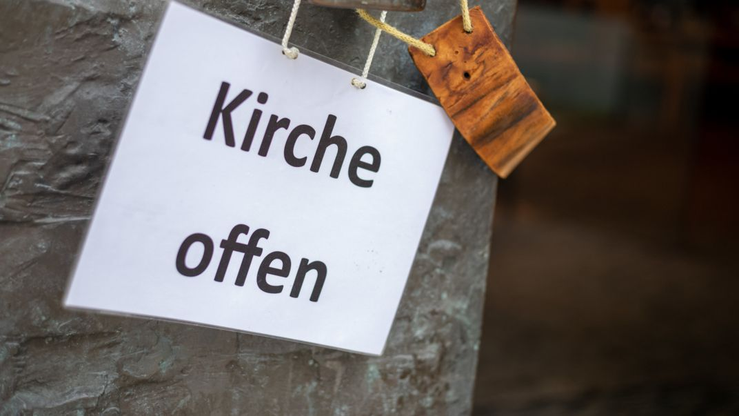 """Ein Schild mit der Aufschrift """"Kirche offen"""" hängt am Haupteingang einer Kirche."""